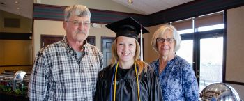 Mom and dad with daughter in graduation cap and gown